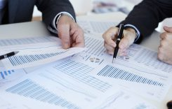 Businessmen examining documents with financial data